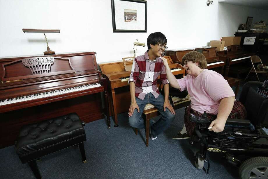 Piano teacher Linda Camann(right) shares a humorous moment with student Robbie Elefante, 20, during a rehearsal at her home on Saturday, Mar. 11, 2017. Camann has been preparing her students for an upcoming performance at the Empire Theatre on March 26. Camann has spent her adult life teaching children with disabilities through her non-profit LGSM Foundation named for the teacher, Lillian Gertrude Sims McRitchie, who had an impact upon her life. Elefante, who has a heart condition, credits Camann for his growth as a person and as a pianist.  (Kin Man Hui/San Antonio Express-News) Photo: Kin Man Hui, Staff / San Antonio Express-News / ©2017 San Antonio Express-News