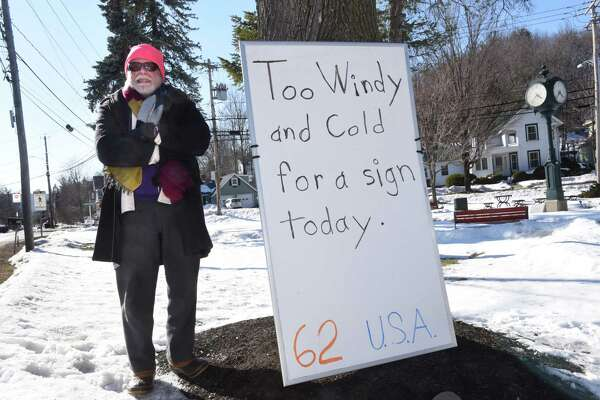 """Stephen Tompkins of Voorheesville stands by his sign where he usually has his views on President Donald Trump while standing in front of the park on Maple Ave. on Wednesday, March 22, 2017 in Voorheesville, N.Y. Today his sign read """"Too windy and cold for a sign today."""" ( Lori Van Buren / Times Union)"""