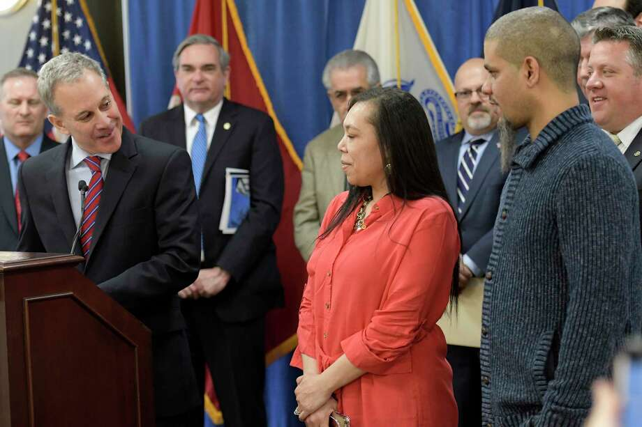 First-time homebuyer Saretha Sotomayor, center stands with her husband Luis, right, as recipients at the announcement by Attorney General Eric Schneiderman, left, of $20 million in grants to 19 land banks that uses the funds to rebuild neighborhoods across the State Friday March 24, 2017 in Albany, N.Y.  Over &1 million is earmarked for Albany County.  (Skip Dickstein/Times Union) Photo: SKIP DICKSTEIN / 20040037A