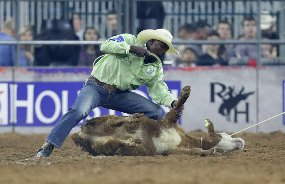 Cory Soloman, of Prairie View, ties down a steer during the tie-down roping wild card competition at the Houston Livestock Show and Rodeo at NRG Park, Friday, March 24, 2017, in Houston. ( Karen Warren / Houston Chronicle ) Photo: Karen Warren/Houston Chronicle