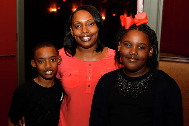 """Tamara Ford, center, with children Martavius, 10, and A'Driauna, 9, at Classic Movie Night at the Jefferson Theatre on Friday night. The theater showed """"Weekend at Bernie's.""""  Photo taken Friday 3/24/17 Ryan Pelham/The Enterprise"""