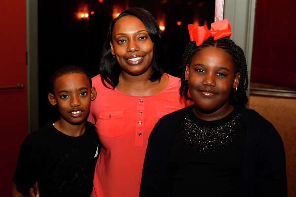"Tamara Ford, center, with children Martavius, 10, and A'Driauna, 9, at Classic Movie Night at the Jefferson Theatre on Friday night. The theater showed ""Weekend at Bernie's.""  Photo taken Friday 3/24/17 Ryan Pelham/The Enterprise"