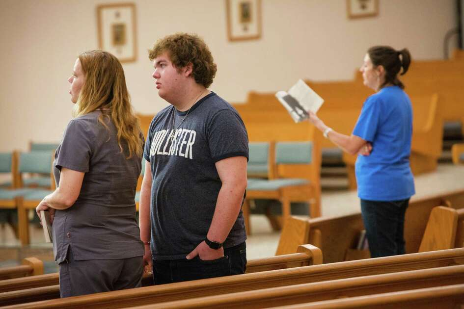 travis kindkead, 14 and his mother Diane pray at the St Ann's Catholic Church in La Vernia, Texas.