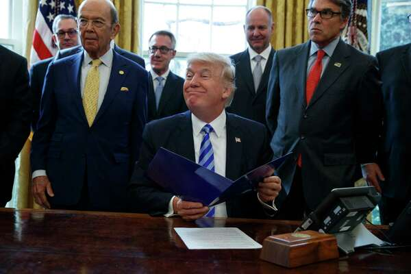 President Donald Trump, flanked by Commerce Secretary Wilbur Ross, left, and Energy Secretary Rick Perry, is seen in the Oval Office of the White House in Washington Friday, March 24, 2017, during the announcing of the approval of a permit to build the Keystone XL pipeline, clearing the way for the $8 billion project. (AP Photo/Evan Vucci) ORG XMIT: DCEV106