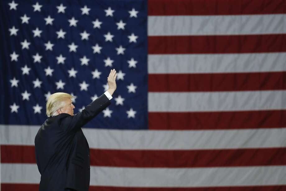 President Trump waves in front of an American flag as he leaves after speaking during a rally at the Kentucky Exposition Center on Monday in Louisville, Ky. Photo: John Minchillo, Associated Press