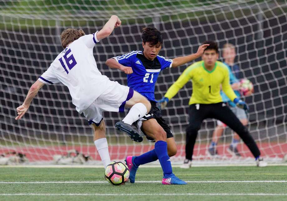 New Caney Keith Osorio (21) fights for the ball agasint Port Neches-Groves midfielder Colton Stone (16) as New Caney goalie Jordy Torres (1) watches during the first period of a Region III-5A b-district high school boys soccer playoff match at Turner Stadium Friday, March 24, 2017, in Humble. PNG defeated New Caney 5-0. Photo: Jason Fochtman, Staff Photographer / © 2017 Houston Chronicle