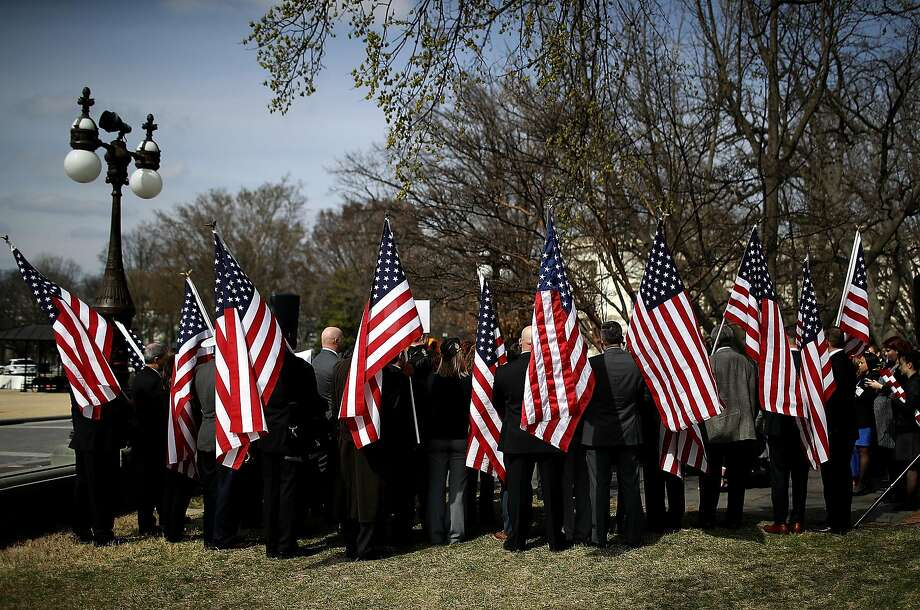 Veterans hold American flags during a news conference to introduce the Deborah Sampson Act at the U.S. Capitol on March 21, 2017 in Washington, DC. AThe legislation addresses issues that female veterans face when they seek healthcare. Photo: Justin Sullivan, Getty Images