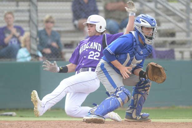 Midland High's Chris Sims (22) slides in to score against Frenship catcher Zariah Pacheco on March 24, 2017, at Zachery Field.  James Durbin/Reporter-Telegram
