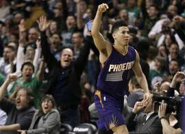 Phoenix Suns guard Devin Booker gestures after he scored a basket, as fans cheer him at TD Garden in the fourth quarter of the Suns' NBA basketball game against the Boston Celtics, Friday, March 24, 2017, in Boston. Booker scored 70 points, but the Celtics wonp 130-120. Booker is just the sixth player in NBA history to score 70 or more points in a game. (AP Photo/Elise Amendola)
