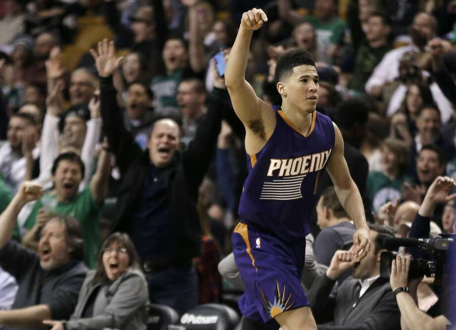 Phoenix Suns guard Devin Booker gestures after he scored a basket, as fans cheer him at TD Garden in the fourth quarter of the Suns' NBA basketball game against the Boston Celtics, Friday, March 24, 2017, in Boston. Booker scored 70 points, but the Celtics wonp 130-120. Booker is just the sixth player in NBA history to score 70 or more points in a game. (AP Photo/Elise Amendola) Photo: Elise Amendola, Associated Press