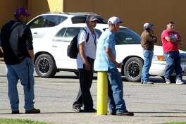 Men wait seeking work near El Ahorro Supermarket on South Main Street Tuesday in Conroe.