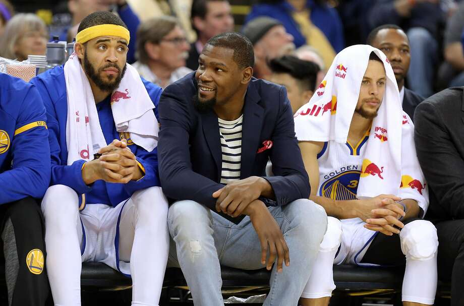 Warriors' Kevin Durant, (center) joins fellow players Javale McGee, 1 and Stephen Curry, 30 on the bench as the Golden State Warriors take on the Sacramento Kings in NBA action at Oracle Arena in Oakland, Ca., on Fri. March 24, 2017. Photo: Michael Macor, The Chronicle