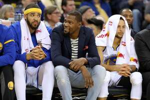 Warriors' Kevin Durant, (center) joins fellow players Javale McGee, 1 and Stephen Curry, 30 on the bench as the Golden State Warriors take on the Sacramento Kings in NBA action at Oracle Arena in Oakland, Ca., on Fri. March 24, 2017.