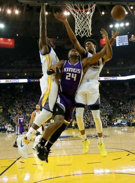 Warriors' Draymond GReen, 23 and Patrick McGraw, 00 stop a shot by the Kings' Buddy Hield, 24 in the first half, as the Golden State Warriors take on the Sacramento Kings in NBA action at Oracle Arena in Oakland, Ca., on Fri. March 24, 2017.