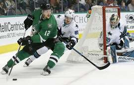Dallas Stars center Radek Faksa (12) skates with the puck against San Jose Sharks left wing Mikkel Boedker (89) and and goalie Aaron Dell (30) during the first period of an NHL hockey game in Dallas, Friday, March 24, 2017. (AP Photo/LM Otero)