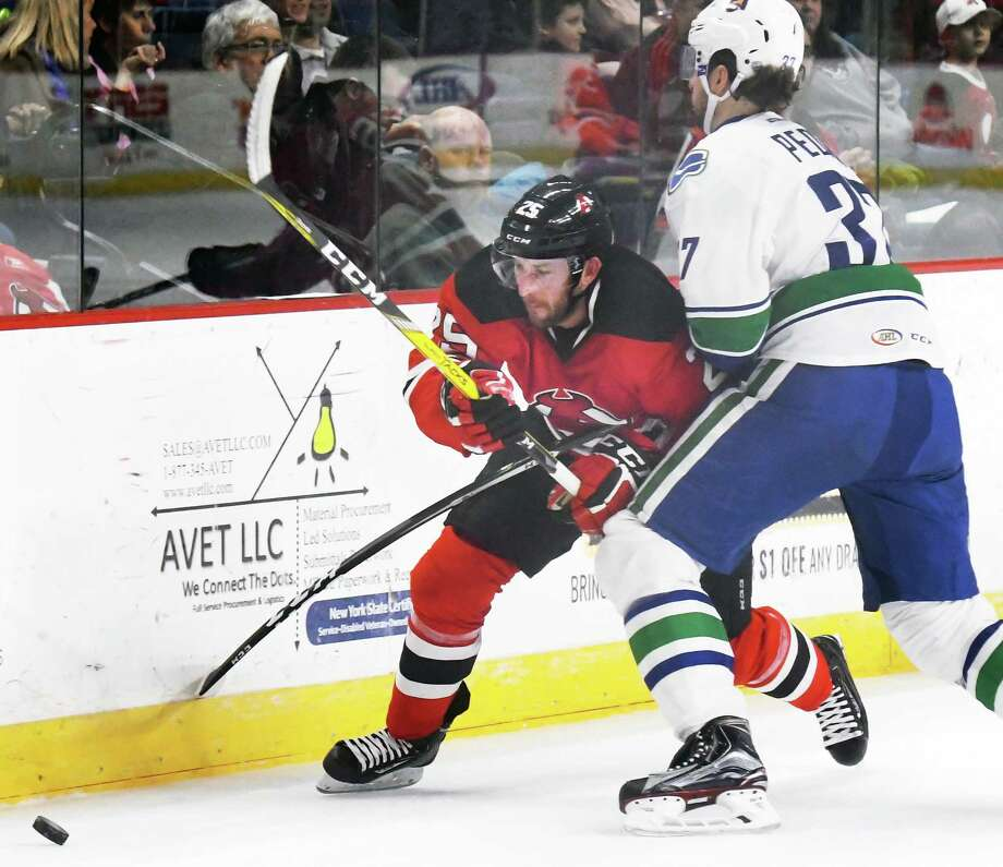 Albany Devils' #25 Nick Lappin, left, fights past Utica Comets' #37 Andrey Pedan during Friday's game at the Times Union Center March 24, 2017 in Albany, NY.  (John Carl D'Annibale / Times Union) Photo: John Carl D'Annibale / 20039358A