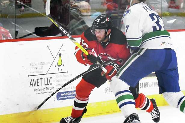 Albany Devils' #25 Nick Lappin, left, fights past Utica Comets' #37 Andrey Pedan during Friday's game at the Times Union Center March 24, 2017 in Albany, NY.  (John Carl D'Annibale / Times Union)