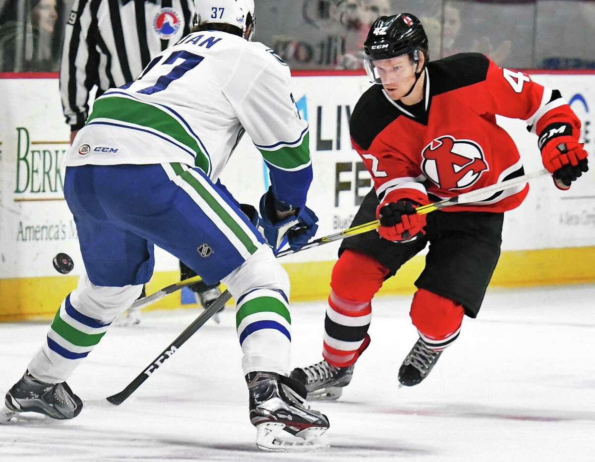 Albany Devils' #42 Greg Wolfe gets the puck past Utica Comets' #37 Andrey Pedan, left, during Friday's game at the Times Union Center March 24, 2017 in Albany, NY. (John Carl D'Annibale / Times Union)