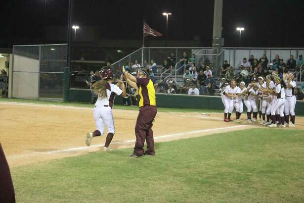 Maleah Olvera receives congratulations from coach Errica Cantu, while a welcoming committee waits for her at home plate, following her two-run homer Friday night that snapped a 1-1 tie.