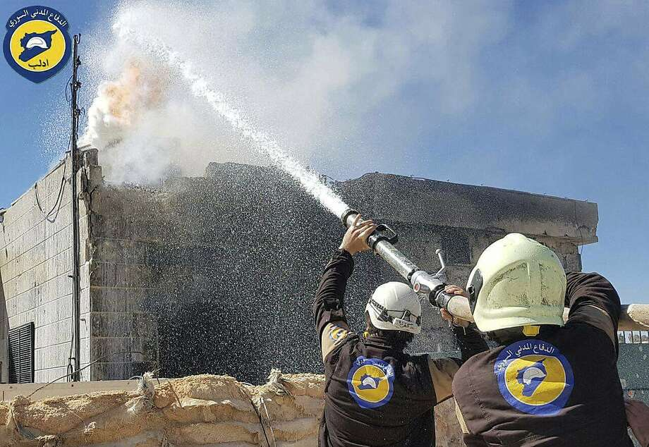 Members of Civil Defense, a group known as the White Helmets, try to extinguish a house fire in Maarat al-Nuaman in Idlib province after an air strike in a photo provided by the group. Photo: Uncredited, Associated Press