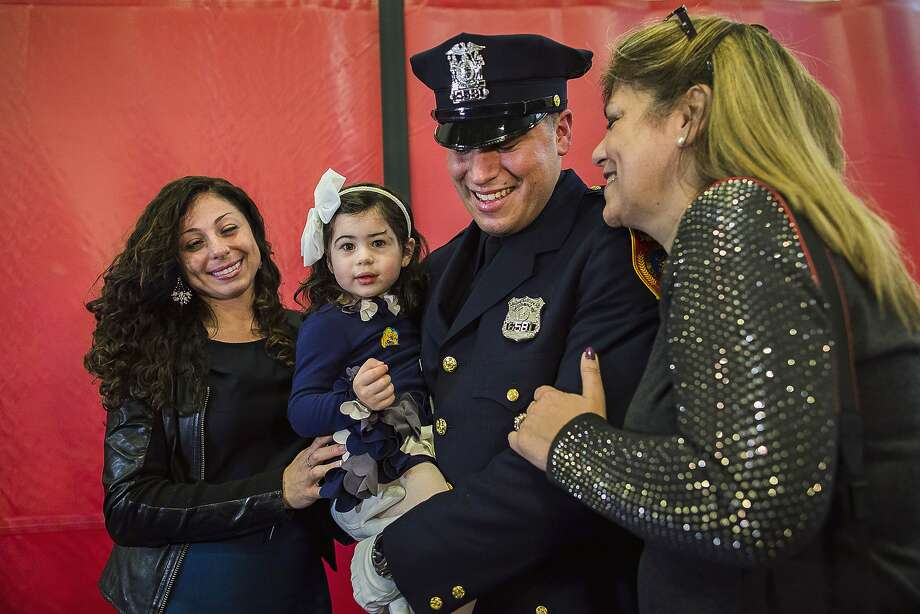 Matias Ferreira celebrates Friday with his daughter, Tianna, his wife, Tiffany (left), and his mother at the Suffolk County Police Academy in Brentwood, N.Y. Photo: Andres Kudacki, Associated Press
