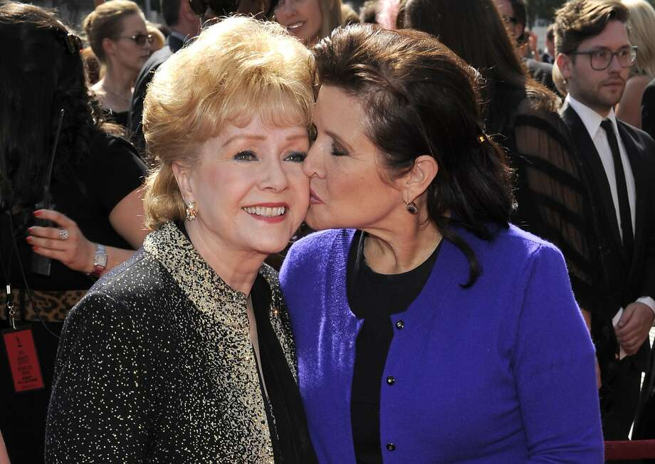 FILE - In this Sept. 10, 2011 file photo, Carrie Fisher kisses her mother, Debbie Reynolds, as they arrive at the Primetime Creative Arts Emmy Awards in Los Angeles. The mother-daughter actresses will be honored at a public memorial on Saturday, March 25, 2017, at the storied Hollywood Hills cemetery where both have been laid to rest. Fisher and Reynolds died one day apart in late December 2016. (AP Photo/Chris Pizzello, File) Photo: Chris Pizzello, Associated Press