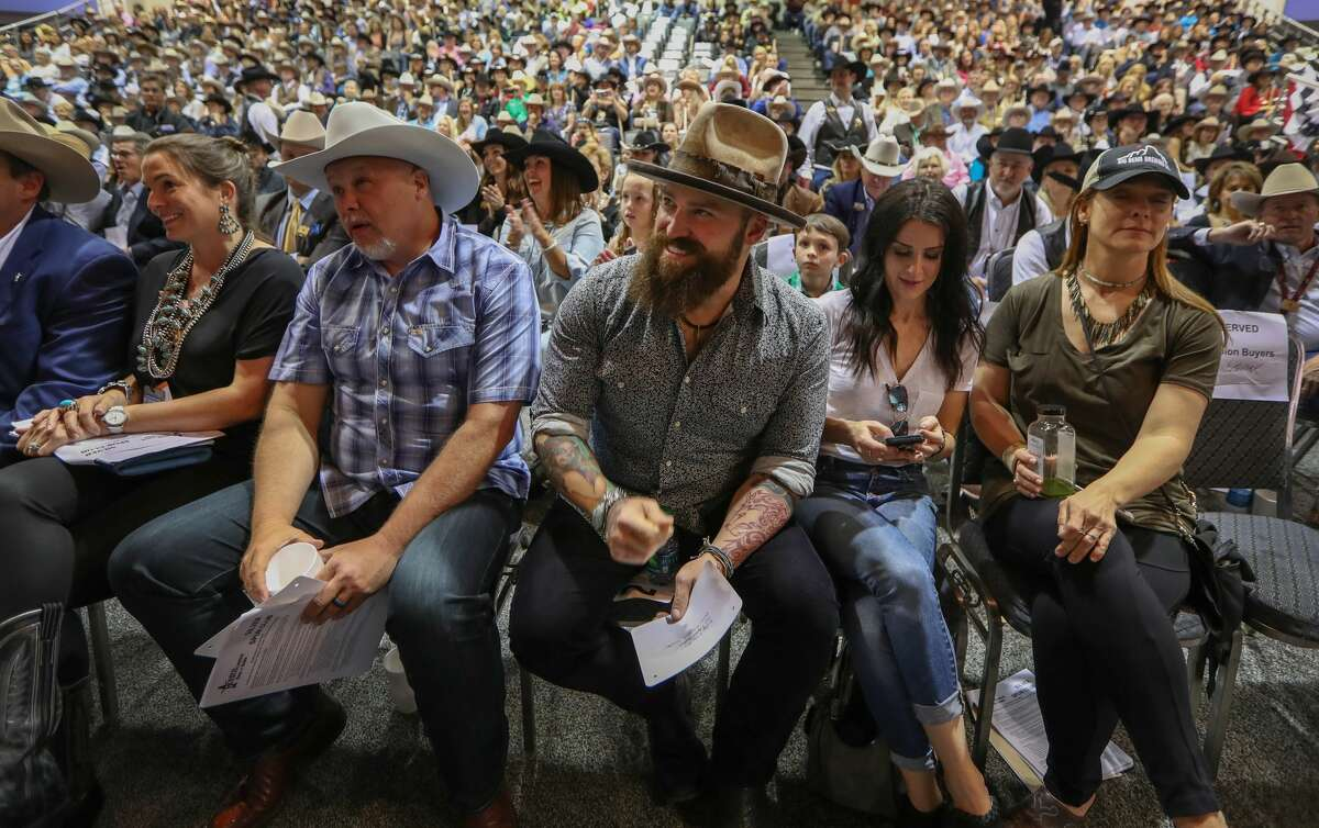 Musician Zach Brown (center) reacts to his winning bid on Stock Martin's Reserve Grand Champion Steer during the Junior Market Steer Auction in NRG Arena Sales Pavilion Saturday, March 25, 2017, in Houston. ( Steve Gonzales / Houston Chronicle )