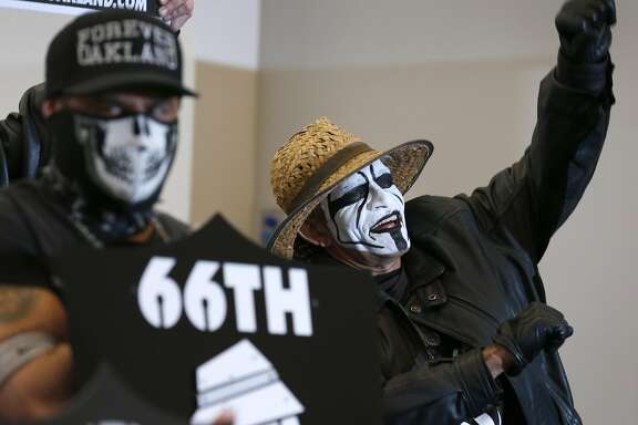Leonard Quinones (right), a member of the Black Hole fan club, joins other diehard Oakland Raiders fans to listen as Mayor Libby Schaaf details a new football stadium plan at a news conference and rally at the Coliseum in Oakland, Calif. on Saturday, March 25, 2017, in a last ditch effort to convince NFL owners to vote down a proposal to relocate the Raiders to Las Vegas.
