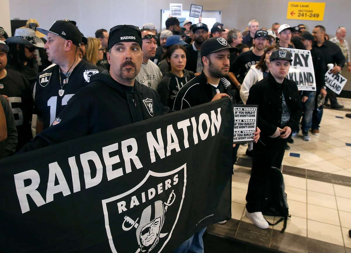 Aaron Kraw unfurls a banner as Oakland Raiders fans listen to Mayor Libby Schaaf outline a new football stadium plan at a news conference and rally at the Coliseum in Oakland on Saturday, March 25, 2017, in a last ditch effort to convince NFL owners to vote down a proposal to relocate the Raiders to Las Vegas.