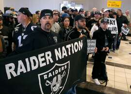 Aaron Kraw unfurls a banner as Oakland Raiders fans listen to Mayor Libby Schaaf outline a new football stadium plan at a news conference and rally at the Coliseum in Oakland, Calif. on Saturday, March 25, 2017, in a last ditch effort to convince NFL owners to vote down a proposal to relocate the Raiders to Las Vegas.