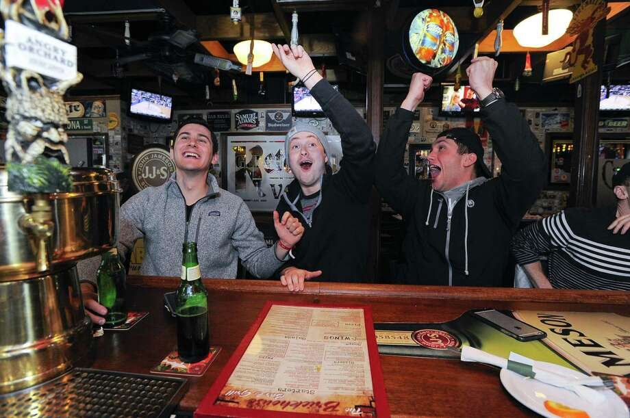 From left, Kevin Eisenberg, Ben Kozera and Michael Icaobelli watch the UConn women's basketball game Saturday at Brickhouse Bar and Grille in Stamford. Photo: Matthew Brown / Hearst Connecticut Media / Stamford Advocate