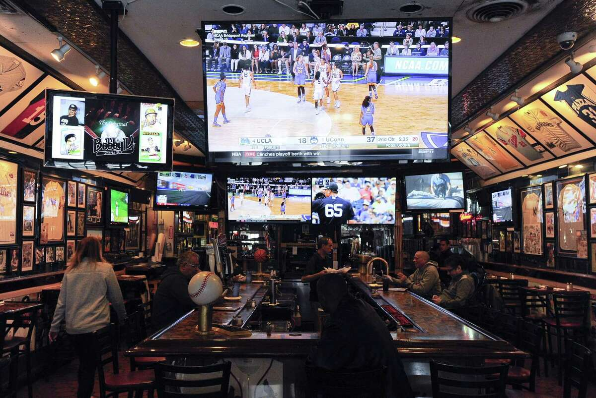 Patrons of Bobby Valentine's Sports Gallery Cafe watch the NCAA Women's Regional Basketball Championships on March 25, 2017 in Stamford, Connecticut.
