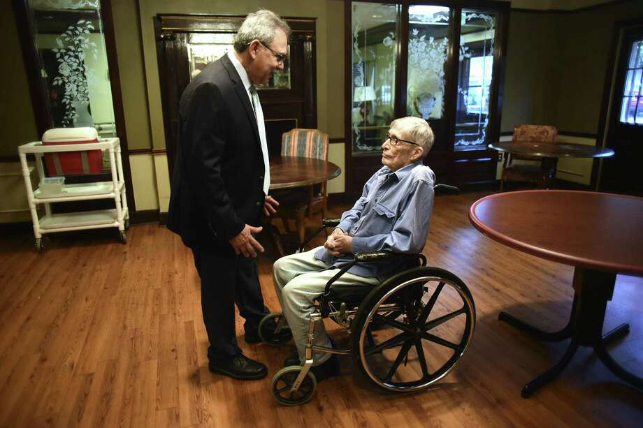 Raul Espinosa Jr., administrator of San Pedro Manor, speaks with resident John Brantley. Seventy percent of the residents there are covered by Medicaid. Photo: Billy Calzada /San Antonio Express-News / San Antonio Express-News