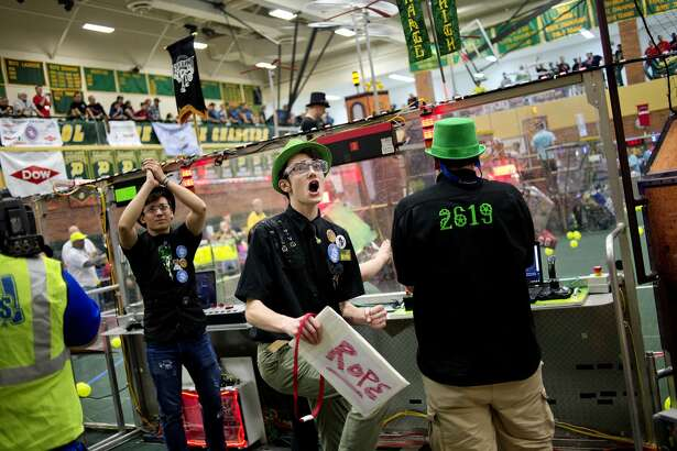 Dow High School's The Charge team member Ethan Poupard, center, celebrates after his team won a semifinal match in a semifinal match during the FIRST (For Inspiration and Recognition of Science and Technology) Robotics District Competition on Saturday at Dow High School.