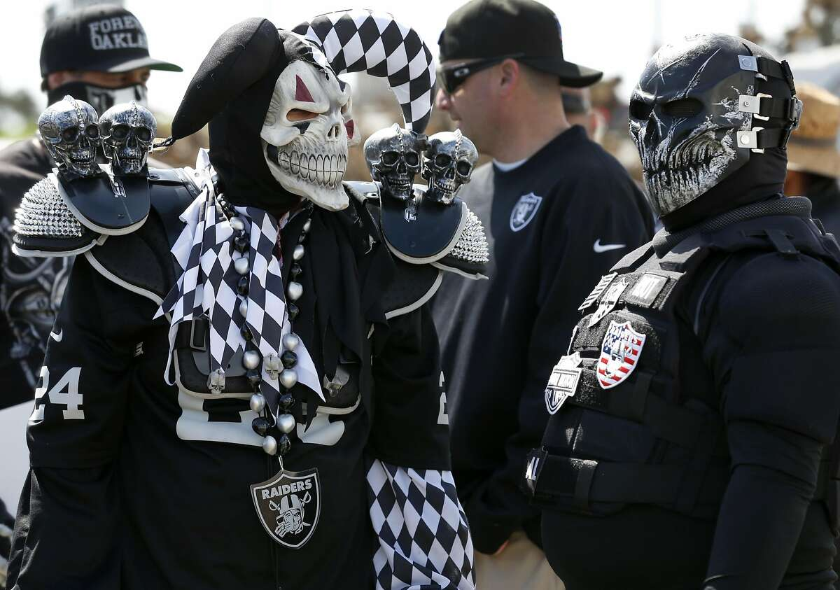 About 50 dedicated Oakland Raiders fans, including Ray Ceja) and Albert Chan gather for a march on 66th Avenue past the Coliseum after Mayor Libby Schaaf provided details of a last minute stadium plan at a news conference in Oakland, Calif. on Saturday, March 25, 2017, hoping to convince NFL owners to reject a proposed relocation of the Raiders to Las Vegas.