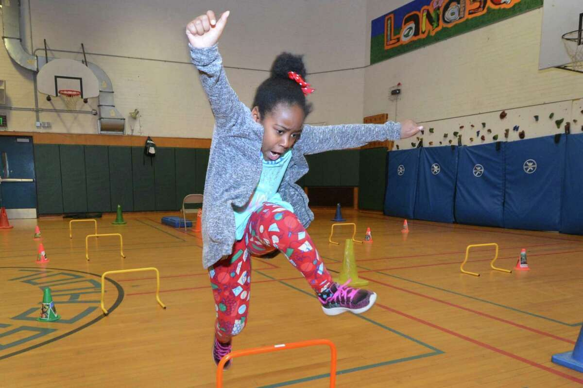 Elisabeth Donkoh makes her way over the hurdle during an obstacle challenge that ends with grabing a plastic piece of food and placing it in the corresponding bag for its food group. Kids learn about nutrition in the Norwalk YMCA after school program at Columbus Magnet School on Wednesday March 22, 2017 in Norwalk Conn