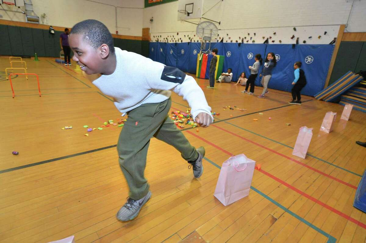 Ameir Spencer gets his choice right and drops a plastic apple into the corresponding bag for its food group fruit, as kids have fun and excercise learning about nutrition in the Norwalk YMCA after school program at Columbus Magnet School on Wednesday March 22, 2017 in Norwalk Conn