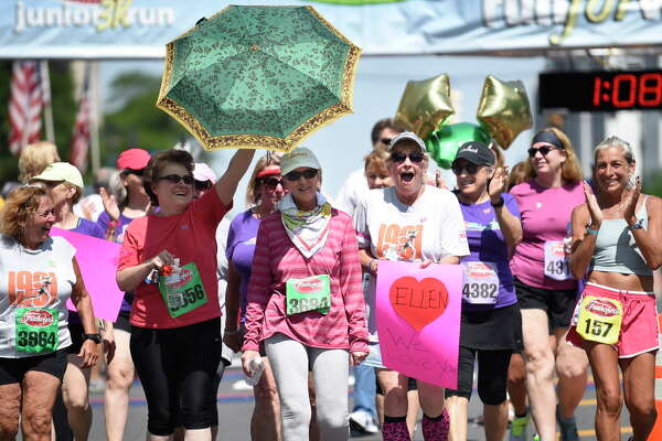 """The """"Fab Five,"""" who've all run this race since 1979, join together at the finish line during Freihofer's 38th Run for Women on Saturday, June 4, 2016, in Albany, N.Y. The women are Cindy Kelly, left, Bernadette LaManna, holding the umbrella for Ellen Picotte, center, Linda Campbell, with the sign, and Denise Herman, far right. (Cindy Schultz / Times Union)"""