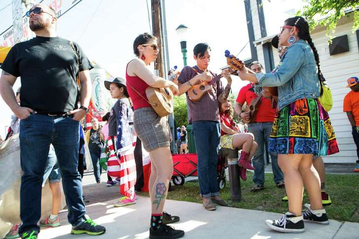 """Keli Rosa Cubanoc leads a group of musicians from the San Antonio cultural center before the Caesar Chavez march begins in west San Antonio, Texas.  The group here is trying to revive the march song """"Non Los Moveran,"""" (they will not move us) that was used back in 1938 in the pecan shelter strike by Emma Tenayuca and later also sang by the Teatro Campesino in the 1960 during Caesar Chavez labor strikes in Claire, Texas. """"We want to bring back this image and the song of the march and we brought our kids to teach them these songs and stand strong and not be moved by racism or by the fact that women are losing their basic reproductive rights. We like to use music to take a stand in the fight,"""" said Cubanoc."""