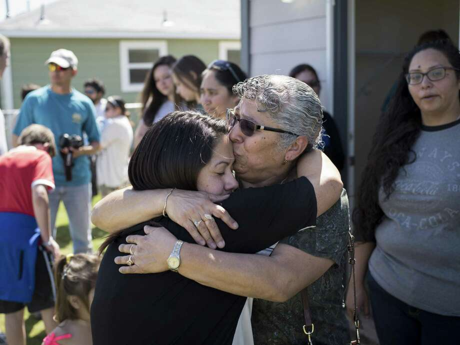 Reyna Guevara, left, hugs her mother Antonia Guevara, center right, as they tour the daughter's new home together for the first time during Habitat for Humanity's dedication of 14 new homes and of their 1000th home in San Antonio on Saturday, March 25, 2017 in San Antonio, Texas. The Guevara's home is the 1000th home to be built in San Antonio. Photo: Matthew Busch, For The San Antonio Express-News / For The San Antonio Express-News / © Matthew Busch
