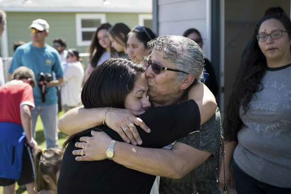 Reyna Guevara, left, hugs her mother Antonia Guevara, center right, as they tour the daughter's new home together for the first time during Habitat for Humanity's dedication of 14 new homes and of their 1000th home in San Antonio on Saturday, March 25, 2017 in San Antonio, Texas. The Guevara's home is the 1000th home to be built in San Antonio.