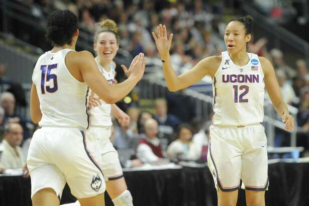 UConn teammates Gabby Williams (15), Katie Lou Samuelson (33), and Saniya Chong (12) celebrate during No. 1 UConn's 86-71 win over No. 4 UCLA in the 2017 NCAA Division I Women's Basketball Championship Regional Semifinal game at Webster Bank Arena in Bridgeport, Conn. Saturday, March 25, 2017.