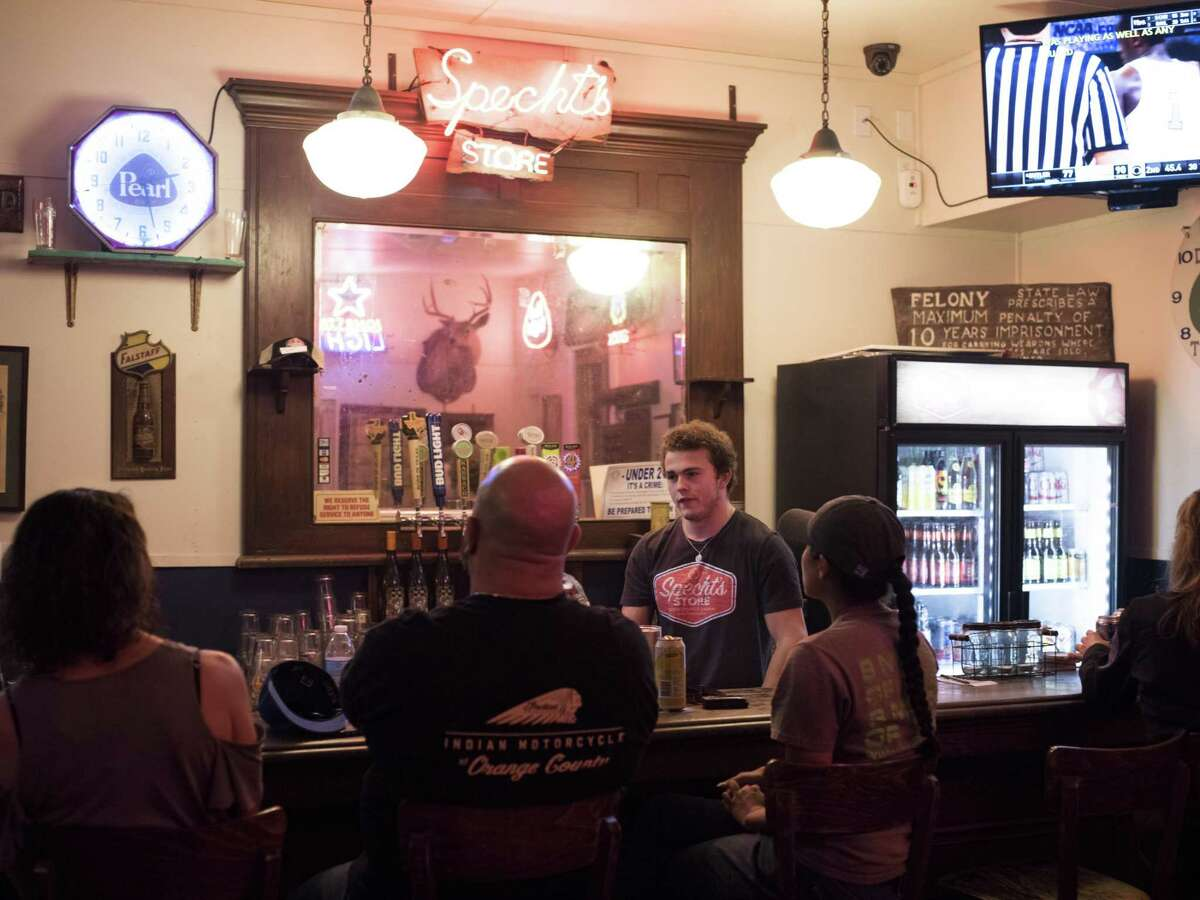 Bartender and son of one of the owners, Travis Gruendler, talks to patrons at Specht's Store in San Antonio on March 24, 2017.