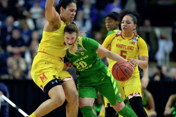Oregon freshman Sabrina Ionescu, center, puts her shoulder into Maryland's Brionna Jones as Ionescu drives to the basket in the second half Saturday.