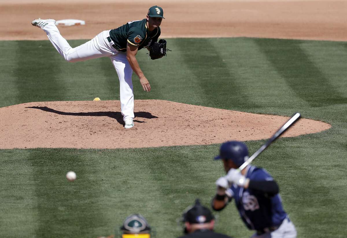 Oakland Athletics starting pitcher Kendall Graveman throws to San Diego Padres' Carlos Asuaje during the third inning of a spring training baseball game, Saturday, March 18, 2017, in Mesa, Ariz. (AP Photo/Matt York)