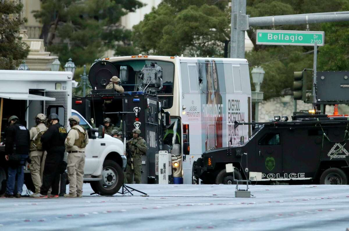 Las Vegas SWAT officers surround a bus along Las Vegas Boulevard, Saturday, March 25, 2017, in Las Vegas. Las Vegas police said the gunman in a fatal shooting on the Strip who barricaded himself inside the public bus has surrendered peacefully after shutting down the busy tourism corridor for hours. (AP Photo/John Locher)