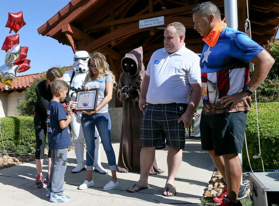 """Mason """"Ace"""" Martinez, 8, reads a plaque held by Kristen Atchley with the Make-A-Wish Foundation saying that he and his family will be going on a Disney cruise during the Mason's Mighty Superhero Run at 239 Colonade Dr in Stone Oak Heights on Saturday, March 25,2017.  Mason, who has been diagnosed with Acute Lymphocytic Leukemia, had decided to raise money for someone else's wish with the fundraising event but was surprised to find he was given one too. With Mason is his mother, Stacy Martinez (from left), a Storm Trooper and Jawa ( Chris Berban and Maria Morrell), Matthew Kostak with Make-A Wish and his father Jeff Martinez.  MARVIN PFEIFFER/ mpfeiffer@express-news.net Photo: Marvin Pfeiffer, Staff / San Antonio Express-News / Express-News 2017"""
