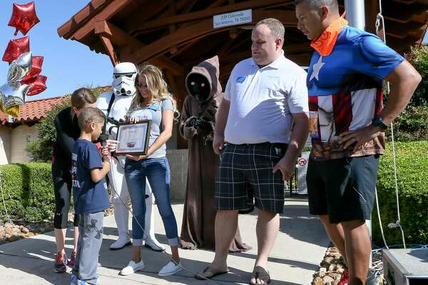 """Mason """"Ace"""" Martinez, 8, reads a plaque held by Kristen Atchley with the Make-A-Wish Foundation saying that he and his family will be going on a Disney cruise during the Mason's Mighty Superhero Run at 239 Colonade Dr in Stone Oak Heights on Saturday, March 25,2017.  Mason, who has been diagnosed with Acute Lymphocytic Leukemia, had decided to raise money for someone else's wish with the fundraising event but was surprised to find he was given one too. With Mason is his mother, Stacy Martinez (from left), a Storm Trooper and Jawa ( Chris Berban and Maria Morrell), Matthew Kostak with Make-A Wish and his father Jeff Martinez.  MARVIN PFEIFFER/ mpfeiffer@express-news.net"""