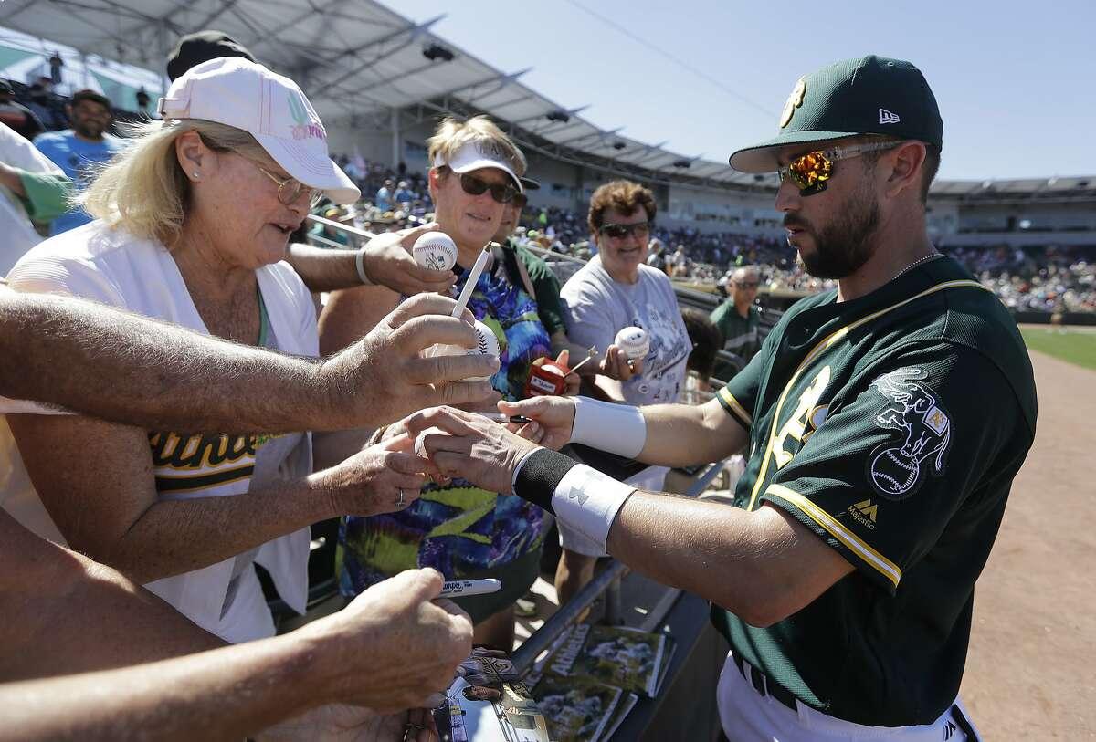 Oakland Athletics' Trevor Plouffe signs autographs for fans before a spring training baseball game Thursday, March 9, 2017, in Mesa, Ariz. (AP Photo/Darron Cummings)