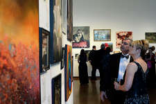 Shaheen and Kerri Farah look at art during the silent auction at the Le Grand Bal fundraiser for Lamar University's College of Fine Arts and Communication on Saturday evening. Photo taken Saturday 3/25/17 Ryan Pelham/The Enterprise